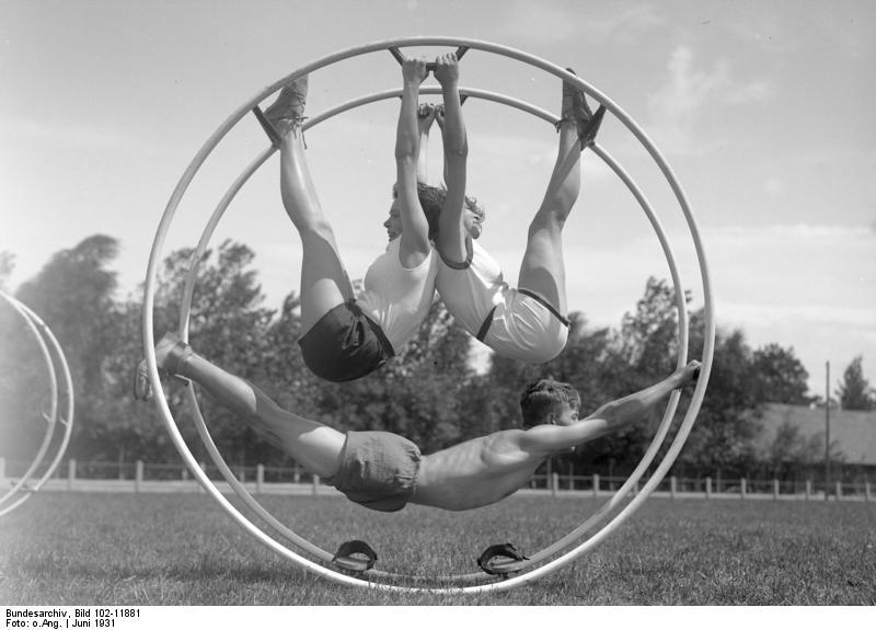 Gymnastische Uebungen am Rhönrad! Mitglieder der Hochschule für Leibesübungen bei gymnastischen Uebungen am Rhönrad, welche den Körper gelenkig und geschmeidig erhalten.