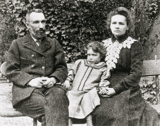 The Curie Family; Marie, Pierre and daughter Irene, sit on an outdoor bench posing for a picture. --- Image by © CORBIS
